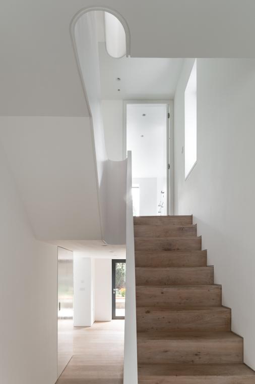 Oak stairs lead up three floors
